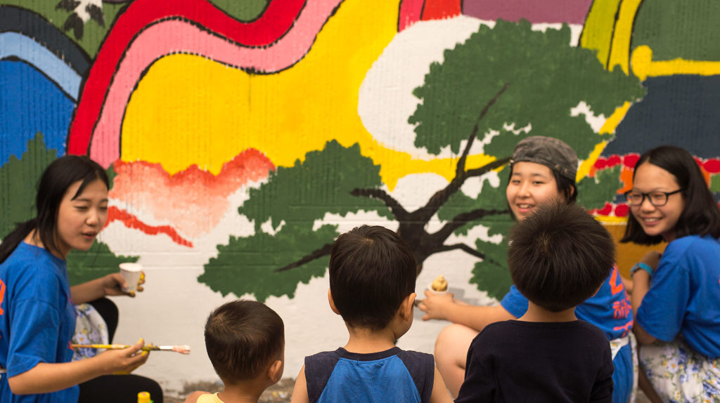 "Children look on as local students paint murals on home in the ""Daedong"" neighborhood in Daejeon, South Korea"