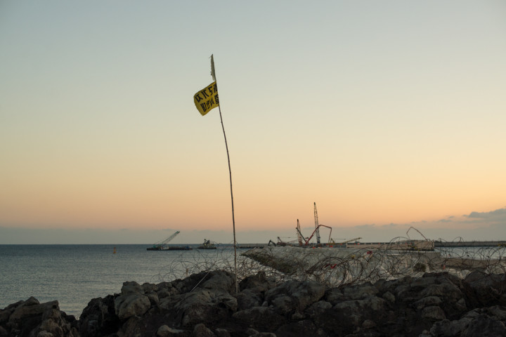 Jeju Naval Base under construction with a protester's flag in the foreground